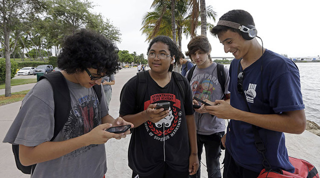 Pokemon Go players Brian Vega, left,  Peyton Ruiz, second from left, and Max Marrero, right, check their smartphones as they try to find Pokemon, Tuesday, July 12, 2016, at Bayfront Park in downto ...