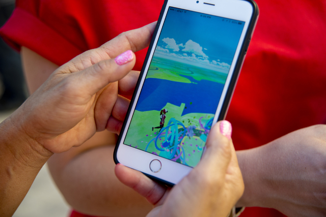 """Chanthy Walsh demonstrates the Pokemon Go app during a Pokemon Go """"Meet and Eat"""" event at Lake Las Vegas on Tuesday, July 19, 2016. The event was organized by Walsh who owns two  ..."""