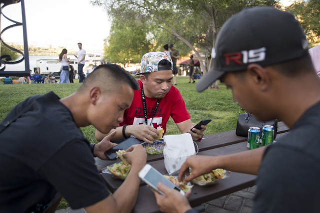 """Ray Vasquez, from left, Carlo Saledo, and Manu Carag use the Pokemon Go app during a """"Meet and Eat"""" event at Lake Las Vegas on Tuesday, July 19, 2016. The event was organized by  ..."""