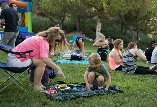 """Christine DeRoss and her son Lane get ready to eat during a Pokemon Go """"Meet and Eat"""" event at Lake Las Vegas on Tuesday, July 19, 2016. The event was organized by Chanthy Walsh  ..."""