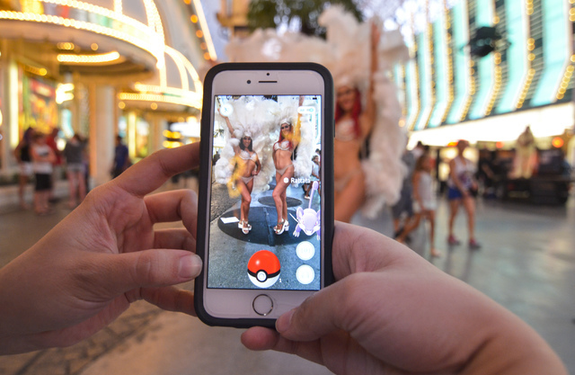 """Review-Journal Digital News Editor Ashley Casper plays """"Pokemon Go"""" as showgirls Cassandra, left, and Christa pose along the Fremont Street Experience in downtown Las Vegas on Wednesday, July 13,  ..."""
