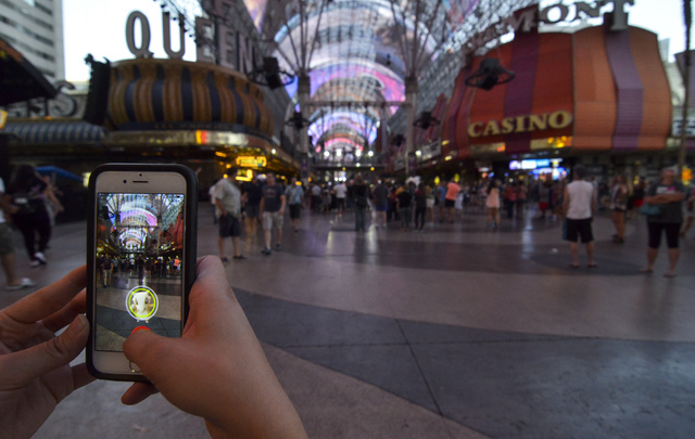 """Review-Journal Digital News Editor Ashley Casper plays """"Pokemon Go"""" along the Fremont Street Experience in downtown Las Vegas on Wednesday, July 13, 2016. (Bill Hughes/Las Vegas Review-Journal)"""