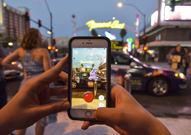 "Review-Journal Digital News Editor Ashley Casper plays ""Pokemon Go"" along the Fremont Street in downtown Las Vegas on Wednesday, July 13, 2016. (Bill Hughes/Las Vegas Review-Journal)"