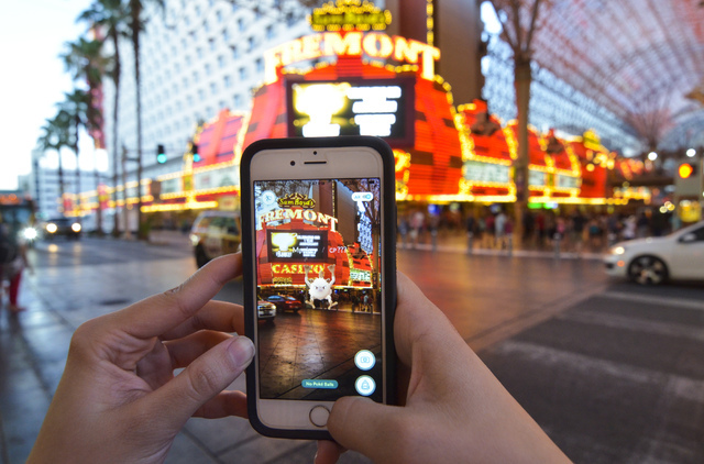 "Review-Journal Digital News Editor Ashley Casper plays ""Pokemon Go"" along the Fremont Street Experience in downtown Las Vegas on Wednesday, July 13, 2016. (Bill Hughes/Las Vegas Review-Journal)"