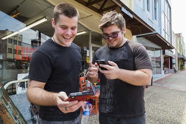 Brothers Jon and Ryan Edmonds play the augmented-reality smartphone game Pokémon Go in downtown Texarkana, Arkansas on Saturday, July 9, 2016. (Joshua Boucher/Texarkana Gazette via AP)