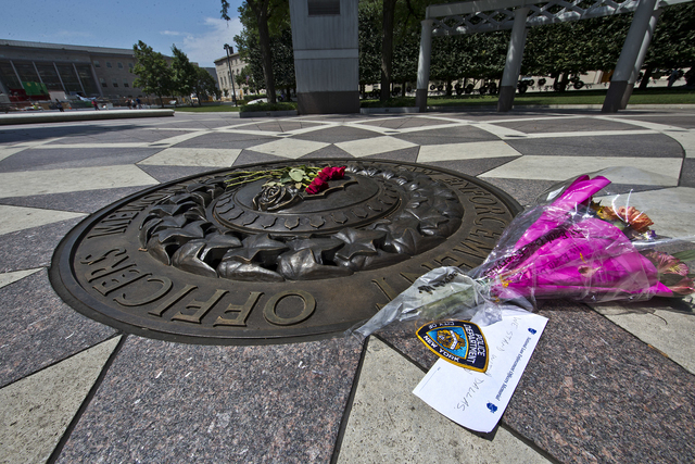 Five red roses on the bronze medallion with another bouquet of flowers and a note in support of the Dallas Police Department are seen at The National Law Enforcement Officers Memorial in Washingto ...