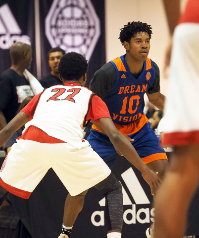 Christian Popoola, Jr., (10) of Team Vision, looks for an open man around defender Tre Gray, (22) of Team Lillard,  the Adidas Summer Championships basketball tournament in Las Vegas, Thursday, Ju ...