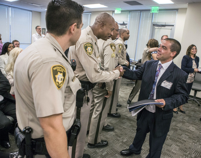 Ex-offender Jamie Cruz shakes hands with Las Vegas police officers during the HOPE for Prisoners graduation ceremony Friday, July 22, 2016, at LVMPD Headquarters at 400 S Martin Luther King Blvd.  ...