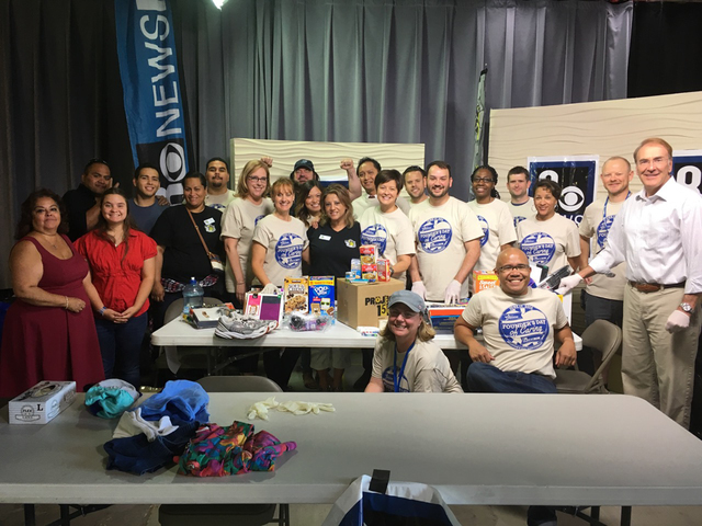 Channel 8 employees and Project 150 volunteers show off the items collected during a donation drive to benefit the nonprofit in June 2016. Special to View