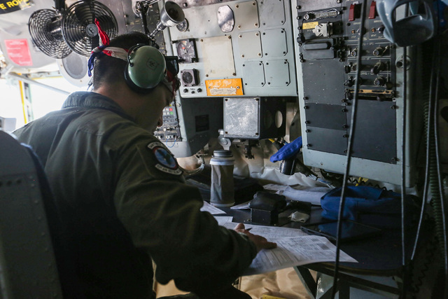Senior Airman Eric Medina, of the 93rd Air Refueling Squadron, finishes paperwork in the cockpit of a KC-135 Stratotanker during a flight over Southern Nevada during a Red Flag exercise on Wednesd ...
