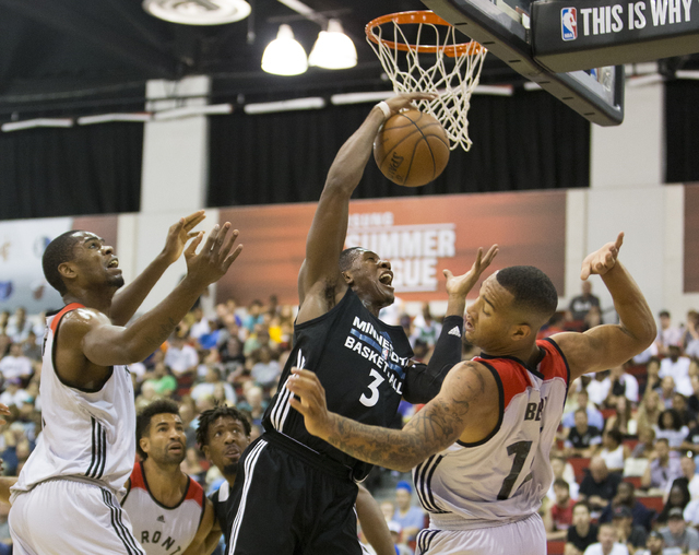 Minnesota Timberwolves guard Kris Dunn (3) grabs a rebound over Toronto Raptors defenders during the NBA Summer League tournament at Cox Pavilion at UNLV on Sunday, July 10, 2016, in Las Vegas. (B ...