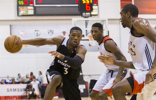 Minnesota Timberwolves guard Kris Dunn (3) drives past Toronto Raptors defenders during the NBA Summer League tournament at Cox Pavilion at UNLV on Sunday, July 10, 2016, in Las Vegas. (Benjamin H ...