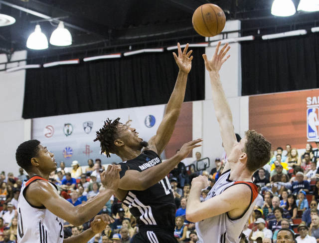 Minnesota Timberwolves forward Jerrid Famous (24) splits Toronto Raptors defenders Bruno Caboclo (20) and  Jakob Poelti (42) during the NBA Summer League tournament at Cox Pavilion at UNLV on Sund ...