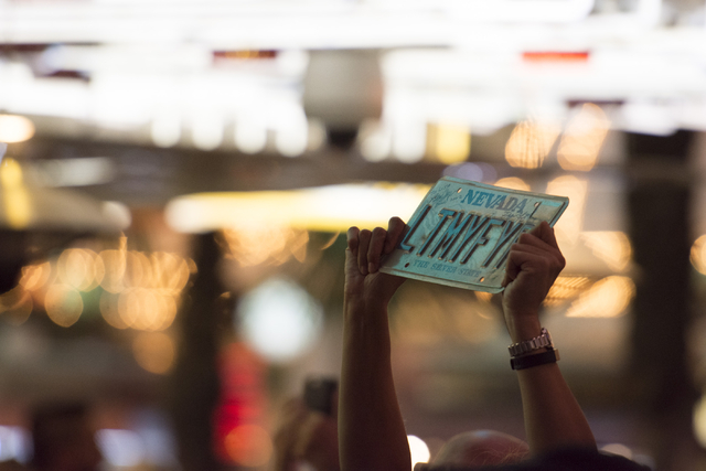 A fan holds up a The Doors themed vanity license plate as Robby Krieger of The Doors performs during the Rock of Vegas concert series at Fremont Street Experience in Las Vegas on Saturday, July 23 ...