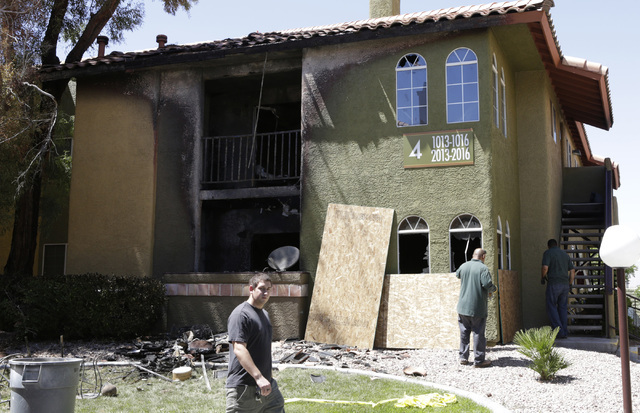 A man walks past as workers board up an apartment damaged by a fire on Monday July 4, 2016. A fire at 9901 W. Sahara Ave., apartment complex displaced four people. Bizuayehu Tesfaye/Las Vegas Revi ...