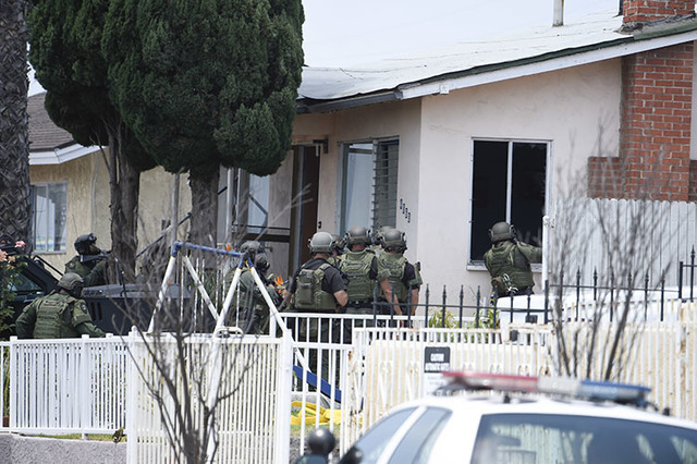 San Diego Police SWAT officers break out windows as they enter a house with a possible suspect inside Friday, July 29, 2016 in San Diego. One San Diego police officer was killed and another was wo ...