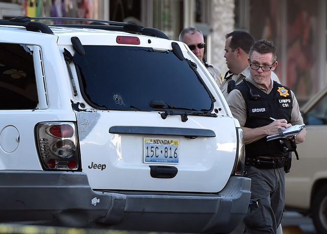 Las Vegas police investigate the scene of a shooting, with a bullet hole seen in the back window of a SUV, at 2204 W. Charleston Blvd. Monday, July 25, 2016, in Las Vegas. David Becker/Las Vegas R ...