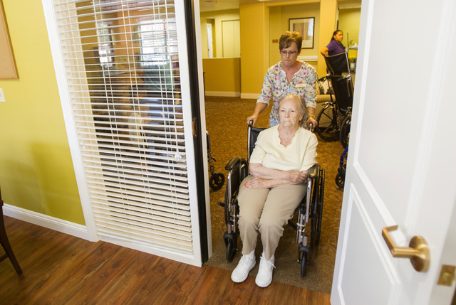 Las Ventanas Life Enrichment Coordinator Diane Edie helps Patricia Mullen, 82, into a room at the continuing care active adult community, 10401 West Charleston Blvd., July 6. Mullen lives in the f ...