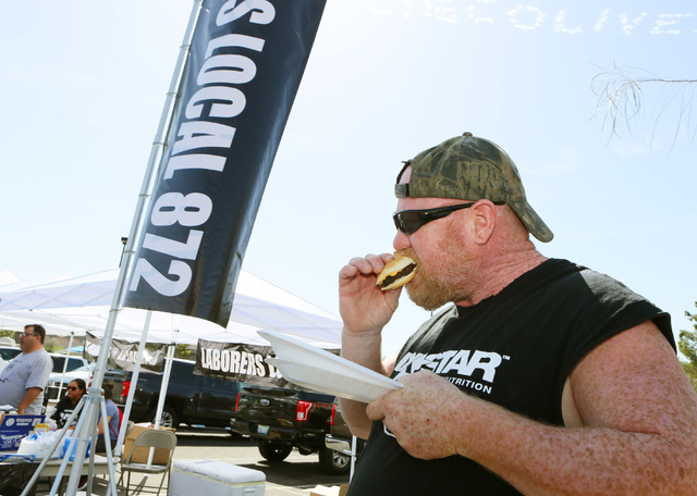 Fireproofer and Raiders football fan Joe Mulvaney eats a hamburger during a cook-out run by Laborers 872 in the parking lot where a meeting of the Southern Nevada Tourism Infrastructure Committee  ...