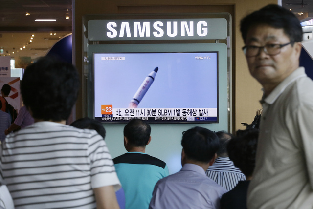 People watch a TV news program showing a file footage of North Korea's ballistic missile that the North claimed to have launched from underwater, at Seoul Railway station in Seoul, South Korea, Sa ...
