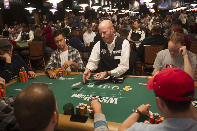 Poker dealer John Holmes, center, deals a hand during Day 4 of the Main Event of the World Series of Poker at the Rio Convention Center in Las Vegas on Friday, July 15, 2016. Richard Brian/Las Veg ...