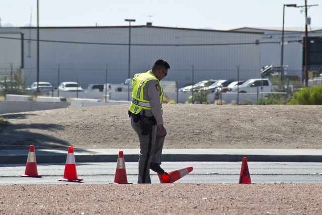 An officer sets up a line of cones to block traffic as police and firefighters investigate a suspicious package near Russell Road and the Interstate 15 in Las Vegas on Saturday, July 9, 2016. (Dan ...