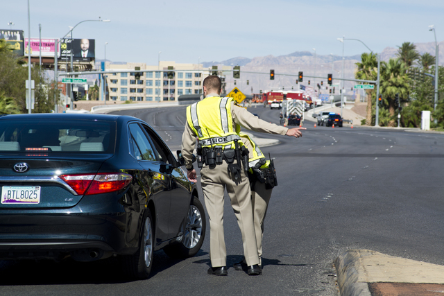 Officers instruct a driver to back up after mistakenly turning on to Russell Road where police and firefighters investigate a suspicious package near Russell Road and the Interstate 15 in Las Vega ...