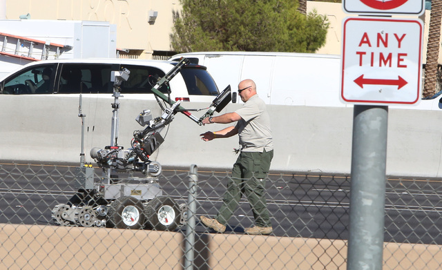 Member of the Las Vegas Fire & Rescue Bomb Squad adjusts the bomb-sniffing robot as Metro police investigate a suspicious package on southbound Interstate 15 near the Hacienda overpass, on Oct ...