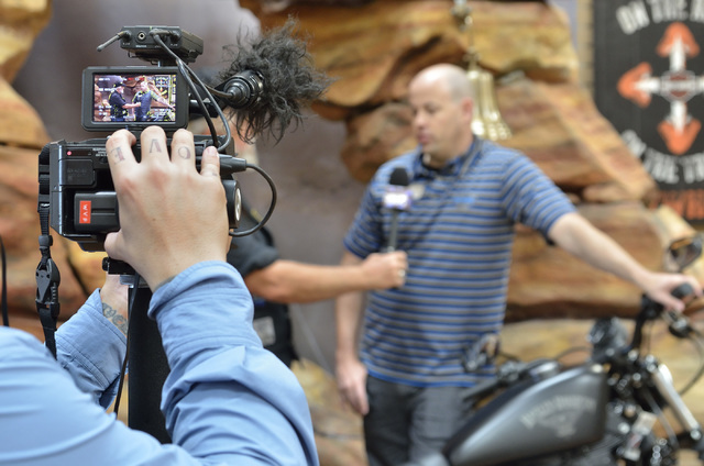 "Cameraman and director Tim Robinson films a segment for ""Temporary Australians"" with executive producer Greg Hirst, in viewfinder at left, and Mike Plehn, general manager of Red Rock Harley Davids ..."