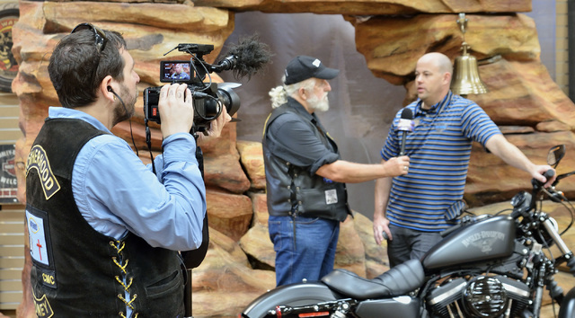 "Australian cameraman and director Tim Robinson, left, and executive producer Greg Hirst, center, are shown with Mike Plehn, general manager of Red Rock Harley Davidson, during filming for "" ..."