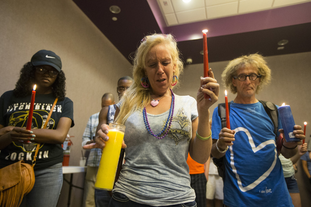 Venus Heard closes her eyes for a prayer during a candlelight vigil honoring the victims of the Orlando mass shooting at The Gay and Lesbian Community Center of Southern Nevada June 12, 2016, in L ...