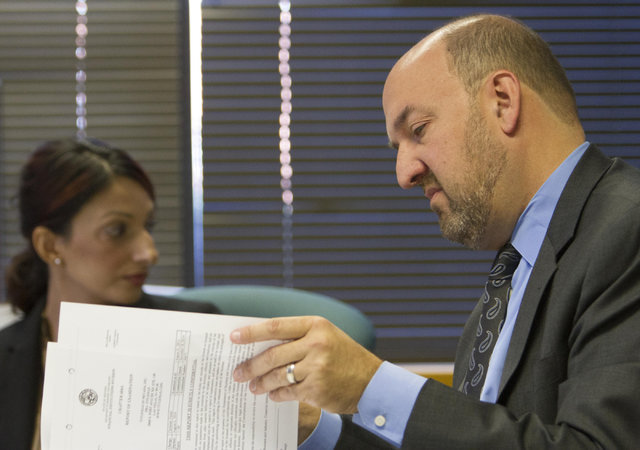 Attorney Patrick Reilly, right, representing TitleMax, looks at his files as he questions Harveen Sekhon, left, supervisory examiner for Nevada's Financial Institutions Division, during a prelimin ...