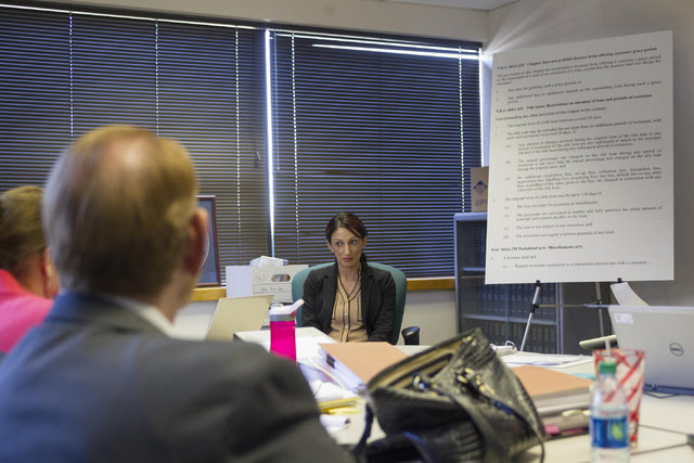 Harveen Sekhon, center, supervisory examiner for Nevada's Financial Institutions Division for non-depository institutions, is seen as she answers questions during a preliminary hearing at the Stat ...