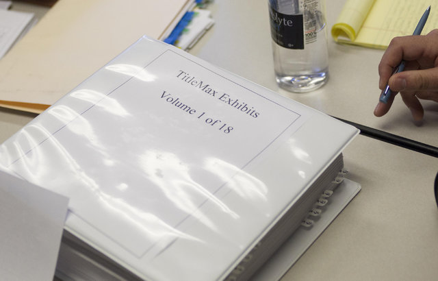 A binder containing TitleMax exhibit evidence is seen during a preliminary hearing at the State of Nevada Financial Institutions Division office located at 2785 Desert Inn Road in Las Vegas on Mon ...