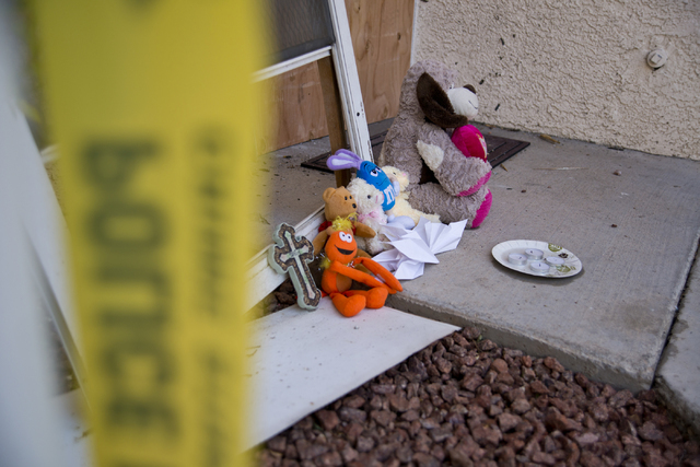 Toys, and other items placed by local residents, sit outside the boarded apartment, where Jason Dej-Oudom killed himself and his three children on Wednesday night, in Las Vegas on Friday, July 1,  ...