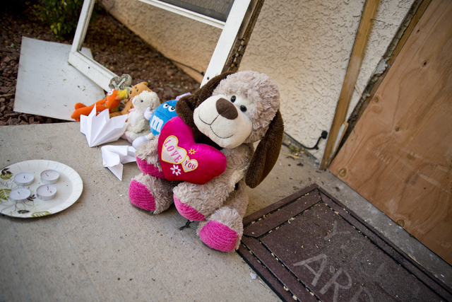 Toys and other items placed by local residents, sit outside the boarded apartment where Jason Dej-Oudom killed himself and his three children on Wednesday night on Friday, July 1, 2016. Dej-Oudom  ...