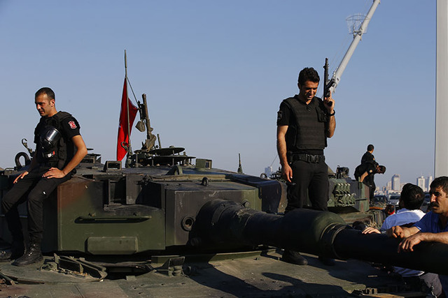Turkish police officers, loyal to the government, stand atop tanks abandoned by Turkish army officers, near Istanbul's iconic Bosporus Bridge, Saturday, July 16, 2016. (Emrah Gurel/The Associated  ...