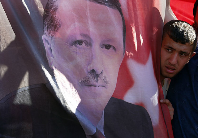 A Turkish man looks towards a portrait of Turkish President Recep Tayyip Erdogan during a protest against the military coup outside Turkey's parliament near the Turkish military headquarters in An ...