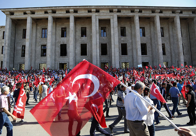 Turkish citizens wave their national flags as they protest against the military coup outside Turkey's parliament near the Turkish military headquarters in Ankara, Turkey, Saturday, July 16, 2016.  ...