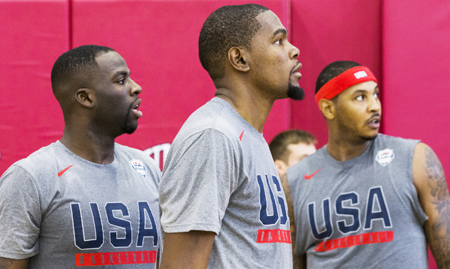 New Golden State Warriors teammates Draymond Green, left, and Kevin Durant, middle, watch team drills during the first day of Team USA basketball practice at the Mendenhall Center at UNLV on Monda ...