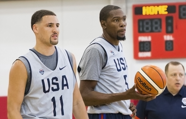 New Golden State Warriors teammates Klay Thompson, left, and Kevin Durant listen to coaches before the start of the first day of Team USA basketball practice at the Mendenhall Center at UNLV on Mo ...