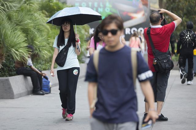A woman walks with an umbrella near The LINQ on Tuesday, June 21, 2016, in Las Vegas. (Erik Verduzco/Las Vegas Review-Journal Follow @Erik_Verduzco)
