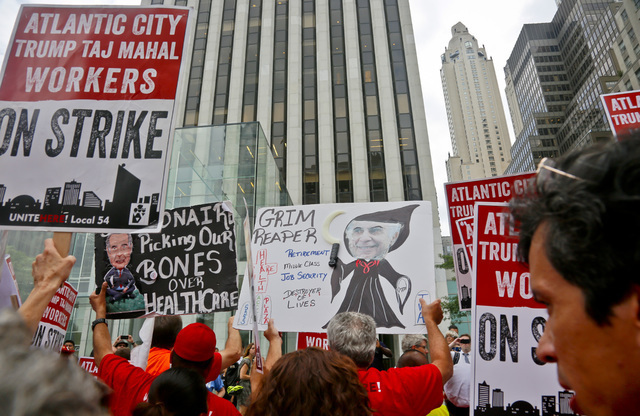 Striking workers from New Jersey's Trump Taj Mahal casino join supporters of Local 54 from the Unite-HERE union to protest outside the Fifth Avenue office of Carl Icahn, Wednesday July 13, 2016, i ...