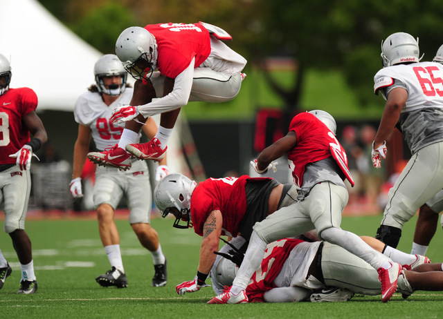 UNLV defensive back Javin White jumps over a pile of tackled players during a scrimmage at UNLV in Las Vegas, Friday August 19, 2016. (Josh Holmberg/Las Vegas Review-Journal)