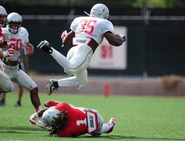 UNLV running back Xzaviar Campbell is tripped up by defensive back Jay'Onn Myles during a scrimmage at UNLV in Las Vegas, Friday August 19, 2016. Josh Holmberg/Las Vegas Review-Journal