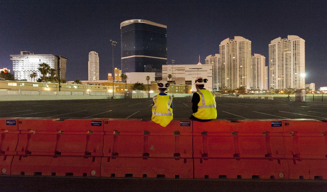 Gino Catania, left, and his cousin Vinny Catania wait on a barrier for the implosion of the remaining tower of the Riviera, far left, along with the property's remaining structures, ea ...