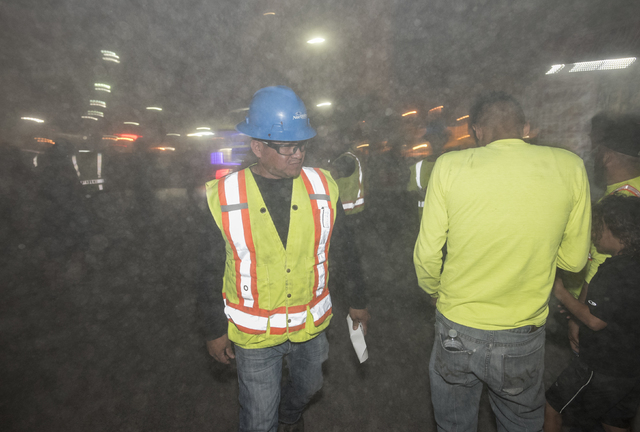 A dust cloud envelops Northstar Contracting Group staff and guests in the aftermath of the implosion of the remaining tower of the Riviera, along with the property's remaining structures, early Tu ...