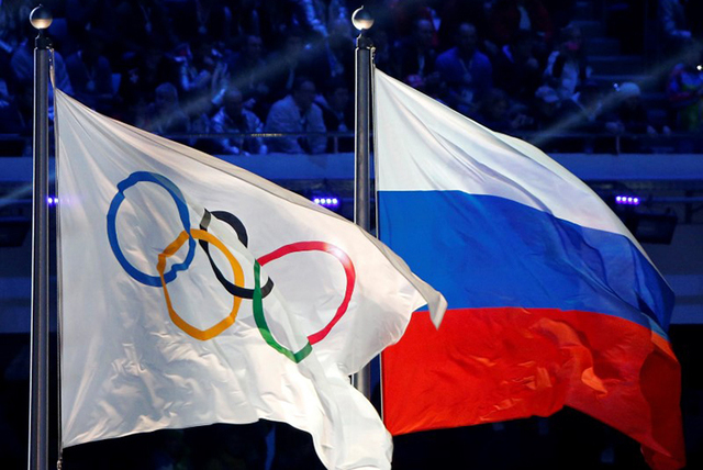 The Russian national flag (R) and the Olympic flag are seen during the closing ceremony for the 2014 Sochi Winter Olympics, Russia, February 23, 2014. (Jim Young/File Photo/Reuters)