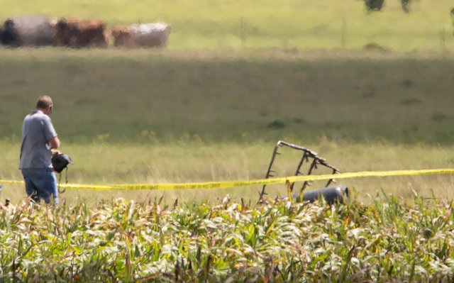 The partial frame of a hot air balloon is visible above a crop field as investigators comb the wreckage of a Saturday morning accident that left 16 people feared dead when the balloon crashed in M ...