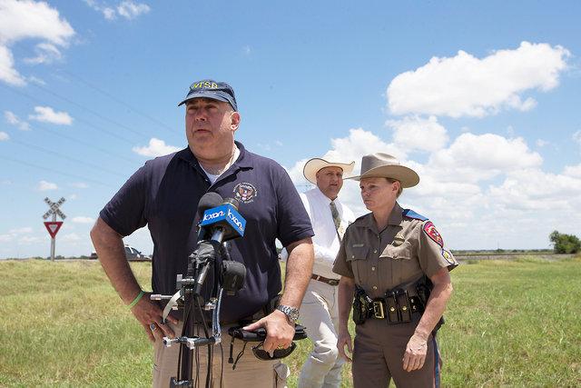 NTSB Senior Advisor Erik Grosof, (L), Caldwell County Sheriff Daniel Law and Texas DPS Trooper Robbie Barrera (R), speak to the media at the scene of a hot air balloon crash in Maxwell, Texas, U.S ...